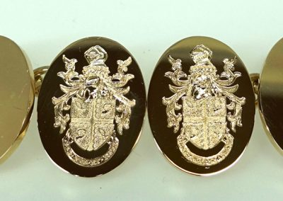 Gold cuff links engraved with coat of arms and motto