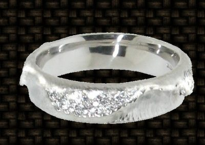 White gold wedding band hand crafted to replicate the surf with 110 small micro set diamonds