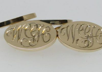 Gold cuff links with entwined initials