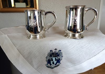 Sterling silver mugs engraved with coat of arms placed on embroidered linen